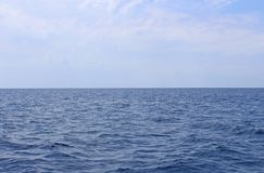 Vista sul mare con l'orizzonte di mare ed il cielo blu profondo quasi chiaro Fondo fotografie stock