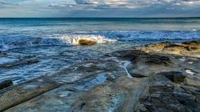 Vista sul mare con le grandi rocce e massi in cielo dell'acqua di mare con le nuvole prima di ampia immagine della pioggia fotografie stock libere da diritti