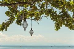 Vista sul mare con le lanterne in albero Fotografie Stock Libere da Diritti