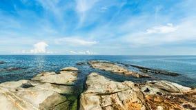 Vista sul mare con le pietre alla spiaggia ed al cielo blu Immagine Stock