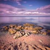 Vista sul mare con le rocce e l'esposizione lunga della sabbia Immagine Stock