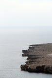 Vista sul mare con una linea rocciosa della costa, al tramonto Fotografie Stock