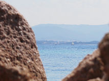Vista sul mare dell'isola di Tavolara sulla priorità alta vaga delle rocce Fotografia Stock Libera da Diritti
