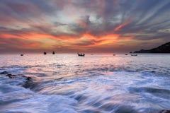 Vista sul mare dell'onda su roccia, esposizione lunga al tramonto sulla spiaggia Fotografie Stock