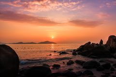 Vista sul mare della natura con i massi, le isole e le onde ad alba arancio splendida fotografia stock libera da diritti
