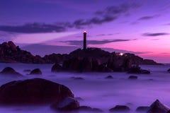 Vista sul mare della natura con le rocce, le onde vaghe e la luce del faro dopo il tramonto immagine stock