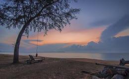 Vista sul mare di alba con l'albero e l'oscillazione Immagini Stock