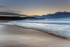 Vista sul mare di alba con la spiaggia ed il promontorio fotografie stock