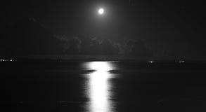 Vista sul mare di notte con la luna ed il cielo nuvoloso Immagine Stock