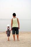 Vista sul mare di sorveglianza del figlio e del padre Immagini Stock