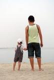 Vista sul mare di sorveglianza del figlio e del padre Immagine Stock