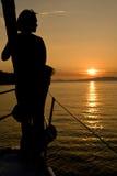 Vista sul mare di tramonto con la siluetta della donna immagini stock libere da diritti