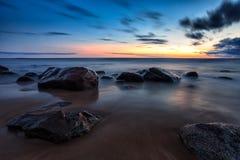 Vista sul mare di tramonto del mare con le rocce bagnate Immagini Stock Libere da Diritti