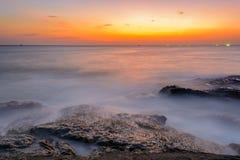 Vista sul mare lunga di esposizione durante il tramonto blu di ora con le rocce come priorità alta Fotografia Stock Libera da Diritti