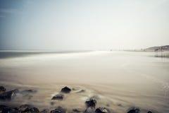 Vista sul mare nebbiosa minimalista con le rocce Immagine Stock