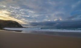 Vista sul mare nuvolosa di alba con il promontorio immagine stock