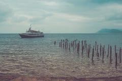 Vista sul mare tonificata di immagine con il cielo nuvoloso, la nave di galleggiamento e l'uccello immagine stock libera da diritti