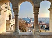 Vista sul Parlamento gotico di Budapest attraverso le colonne del bastione del pescatore fotografia stock