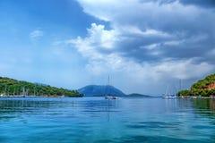 Vista sul porto e sull'isola con le montagne nel villaggio di Vathi Mare ionico dell'isola di Meganisi immagine stock libera da diritti