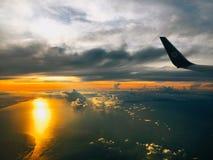 Vista sull'aereo con il cielo ed il tramonto in mare fotografia stock