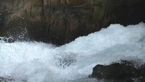Vista sulla corrente rapida del fiume della montagna Intermediazione potente dell'inondazione contro superficie pietrosa che spru stock footage