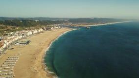 Vista sulla costa atlantica di Nazare e sulla spiaggia sabbiosa nel Portogallo Volo su un fuco stock footage
