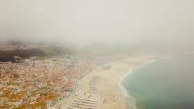 Vista sulla costa atlantica di Nazare e sulla spiaggia sabbiosa nel Portogallo Volo su un fuco nelle nuvole stock footage
