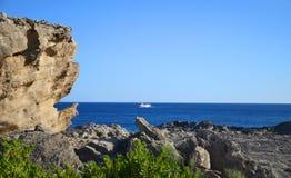 Vista sulla costa, sul cielo blu, sulle rocce e sulla barca Mediterranei Fotografia Stock Libera da Diritti