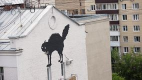 Vista sulla facciata di grande costruzione con l'immagine del gatto nero e di due balconi video d archivio