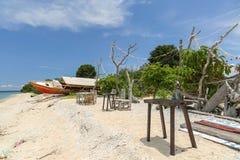 Vista sulla spiaggia con la tavola di legno, le catene di corallo e una barca Immagini Stock Libere da Diritti