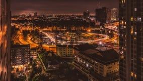 Vista sulla strada principale da Bangkok con i semafori variopinti durante l'ora di punta alla notte da un grattacielo Fotografie Stock