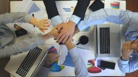 Vista superior às mãos de quatro executivos que comemoram a realização O grupo de empregadores empilhou os braços junto um por um filme