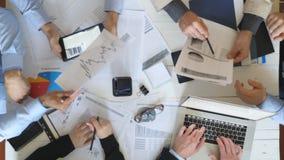 Vista superior às mãos dos homens de negócios que trabalham eficientemente com documentos Grupo de trabalhadores que sentam-se na filme