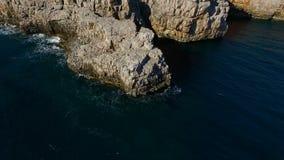 Vista superior aérea: as ondas do mar lavam o litoral rochoso video estoque