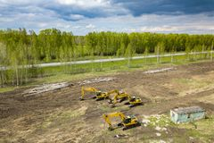 Vista superior aérea de cuatro excavadores amarillos de la correa eslabonada que se colocan en la tierra cerca del emplazamiento  imagen de archivo