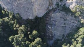 Vista superior aérea de los picos de montaña y del tiro verde del bosque Paisaje hermoso de acantilados, de colinas, y de árboles almacen de metraje de vídeo