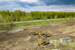 Vista superior aérea de quatro máquinas escavadoras amarelas da esteira rolante que estão na terra perto do canteiro de obras e q imagem de stock