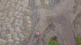 Vista superior aérea de un camión de la extremidad que conduce a la arena y al suelo cargados en un emplazamiento de la obra con  metrajes