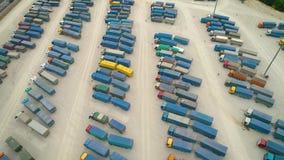 Vista superior aérea del blanco del camión semi con el estacionamiento del remolque del cargo con otros camiones en estacionamien metrajes