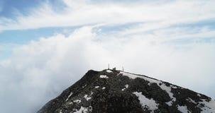Vista superior aérea dianteira sobre a estação meteorológica nebulosa na parte superior da montanha no dia ensolarado com nuvens  filme