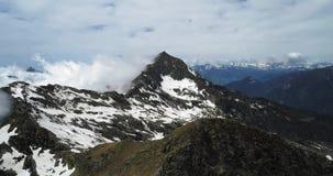 Vista superior aérea dianteira sobre a montanha nevado rochosa nebulosa no dia ensolarado com nuvens Montanhas italianas dos cume filme