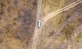 Vista superior aérea do carro na estrada fora da estrada no campo em um dia chuvoso f foto de stock