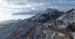 Vista superior aérea inversa sobre o carro que viaja na estrada na montanha da neve do inverno perto das madeiras da floresta Rua video estoque