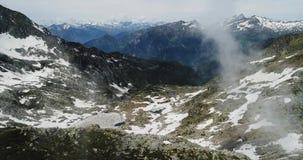 Vista superior aérea lateral sobre a montanha nevado rochosa nebulosa no dia ensolarado com nuvens Montanhas italianas dos cumes  video estoque