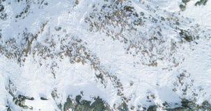 A vista superior aérea aérea sobre a montanha nevado do inverno balança Montanhas rochosas cobertas na geleira da neve e do gelo  filme