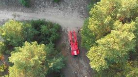 Vista superior al coche de bomberos rojo en una opinión de Forest Aerial del pino que vuela sobre el camino forestal metrajes