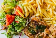 Vista superior ao bife grelhado da galinha seved com vegetais e microplaquetas de batata imagens de stock royalty free