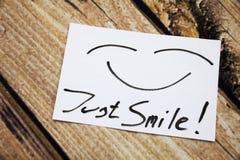 Vista superior apenas de la nota pegajosa de la sonrisa sobre el escritorio de madera con la cara de la sonrisa Fotografía de archivo