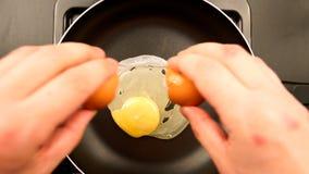 VISTA SUPERIOR: As mãos humanas põem o ovo sobre a frigideira foto de stock royalty free