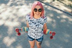 Vista superior bonita disparada da jovem mulher atrativa com cabelo cor-de-rosa e com o longboard na rua, óculos de sol vestindo  imagem de stock royalty free